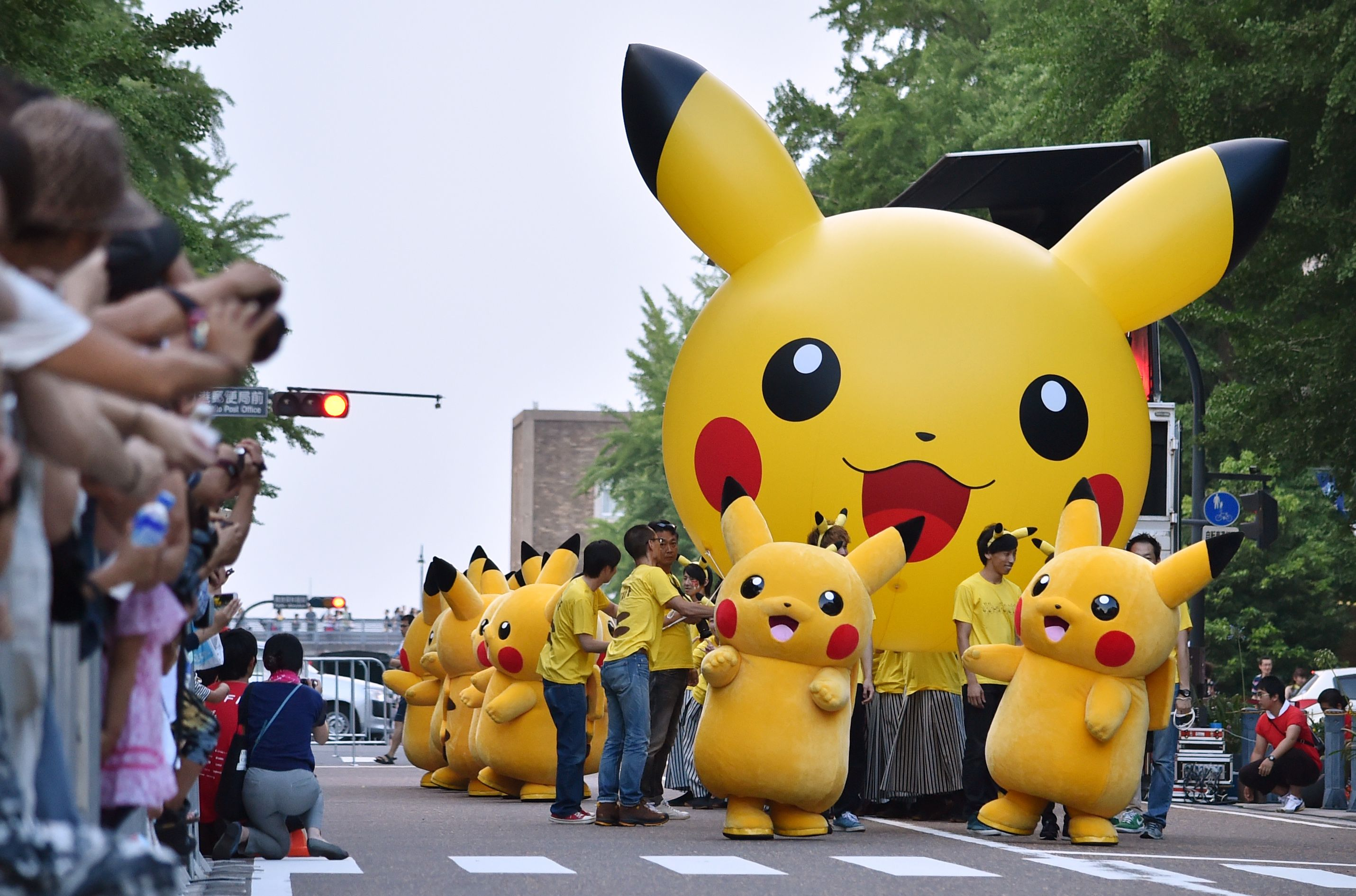 (FILES) This file photo taken on August 2, 2015 shows costumed performers as Pikachu, the popular animation Pokemon series character, performing at the Yokohama Dance Parade in Yokohama. Legions of Pokemon fans were left disappointed on July 20, 2016 after a rumoured release of the franchise's hugely popular smartphone game in Japan proved wrong. / AFP PHOTO / KAZUHIRO NOGI