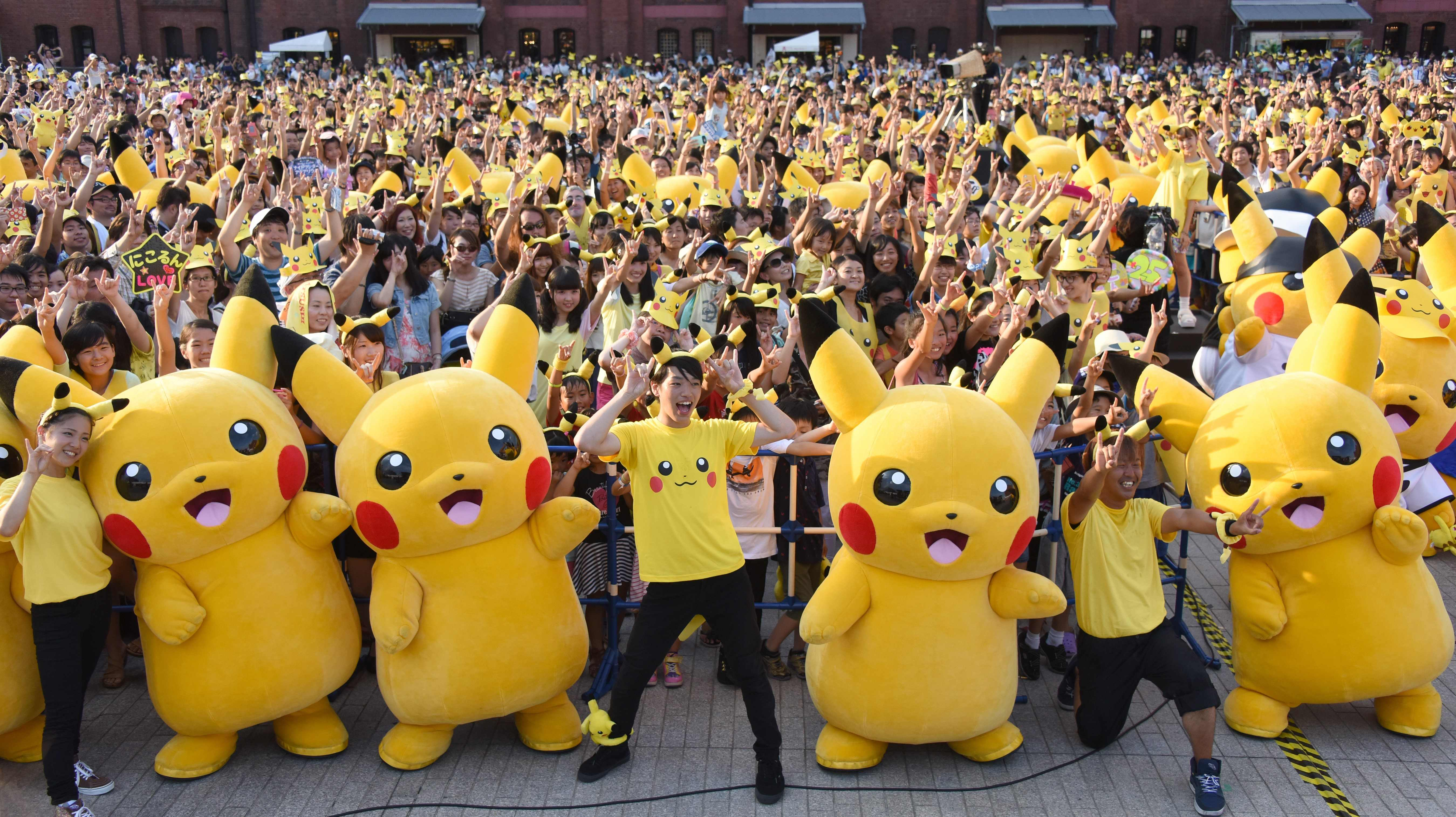 """(FILES) This file picture taken on August 16, 2015 shows dozens of people dressed up as Pikachu, the famous character of Nintendo's videogame software Pokemon, dancing with fans as the final of a nine-day """"Pikachu Outbreak"""" event in Yokohama, in suburban Tokyo. With Pokemon-mania sweeping the planet, Nintendo's nascent shift into mobile gaming has proved a massive hit, vindicating the Japanese videogame giant's decision to unshackle itself from a long-standing consoles-only policy. / AFP PHOTO / TORU YAMANAKA / TO GO WITH Japan-US-IT-Nintendo-Pokemon-lifestyle,FOCUS by Harumi OZAWA"""